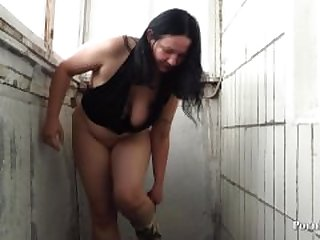 mature woman urinating in a cup.